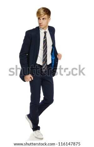 Full length portrait of a stylish young man in suit walking over white background - stock photo