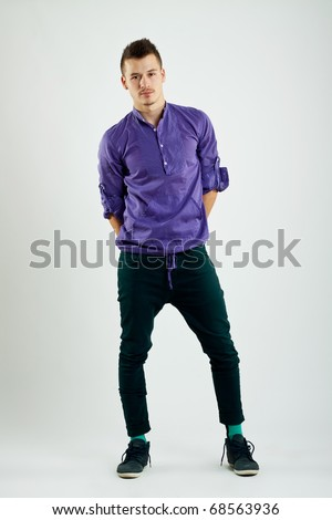 Full length portrait of a stylish young man standing with hands at his back - stock photo