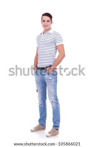 Full length portrait of a stylish young man standing with hands in pockets over white background - stock photo