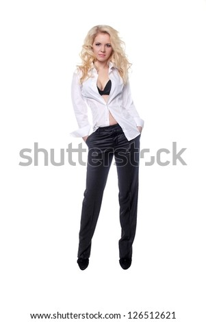 Full length portrait of a stylish young woman in Men style standing with hands in pockets over white background - stock photo