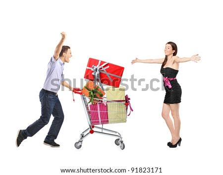 Full length portrait of a surprised  woman with hands wide open and an euphoric male pushing a shopping cart full with gifts isolated on white background