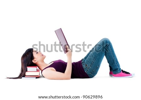 Full length portrait of a teenager lying on the floor, reading with her head resting on books over white background. - stock photo