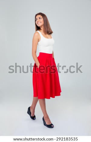 Full length portrait of a thoughtful happy woman in skirt looking up over gray background - stock photo