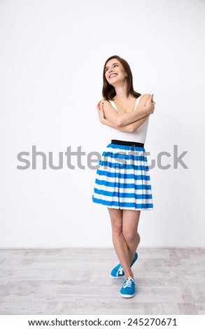 Full length portrait of a thoughtful woman looking up at copyspace - stock photo