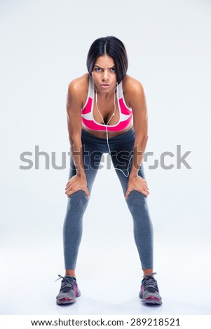 Full length portrait of a tired fitness woman resting over gray background and looking at camera - stock photo