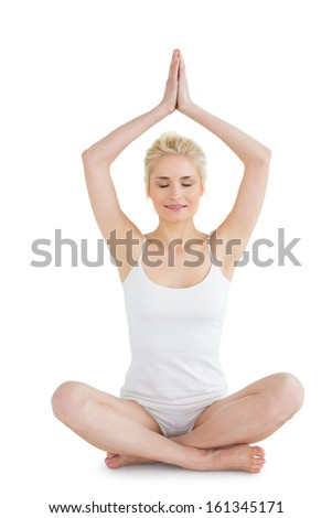 Full length portrait of a toned young woman sitting with joined hands over head against white background