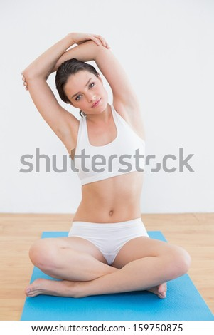 Full length portrait of a toned young woman stretching hand over head in fitness studio - stock photo