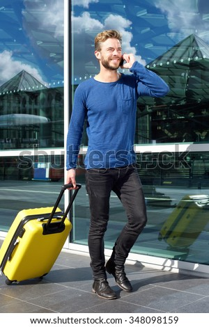 Full length portrait of a traveling man walking and talking on mobile phone - stock photo