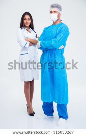 Full length portrait of a two doctors standing isolated on a white background - stock photo