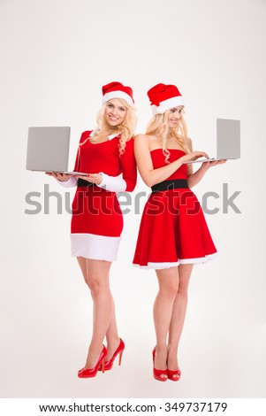 Full length portrait of a two smiling women in santa cloth using laptop computer isolated on a white background - stock photo