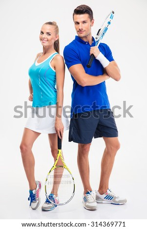 Full length portrait of a two tennis players standing isolated on a white background and looking at camera - stock photo