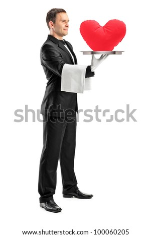 Full length portrait of a waiter holding a tray with a red heart shape on it isolated on white background - stock photo