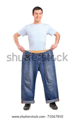 Full length portrait of a weight loss male showing his old jeans isolated on white - stock photo