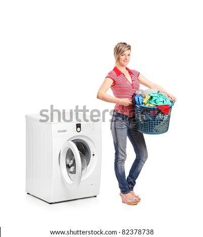 Full length portrait of a woman holding a basket and standing next to a washing machine isolated on white background - stock photo