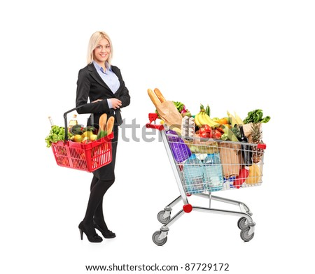 Full length portrait of a woman holding a shopping basket and shopping cart isolated on white background - stock photo