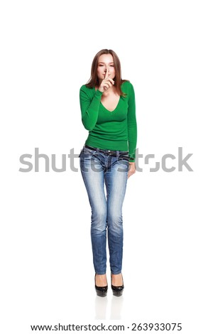 Full length portrait of a woman making silence gesture isolated on white - stock photo