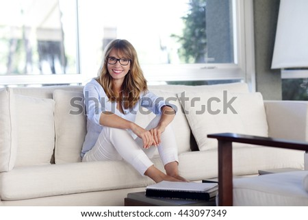 Full length portrait of a woman sitting in relaxing at beautiful living room in modern home. - stock photo