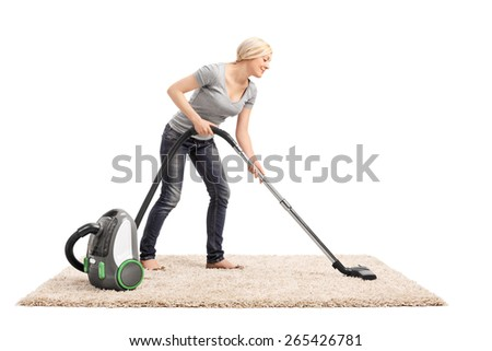 Full length portrait of a woman vacuuming a beige colored carpet with a vacuum cleaner isolated on white background - stock photo