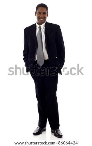 Full length portrait of a young African American businessman standing with his hands in the pockets isolated white background - stock photo