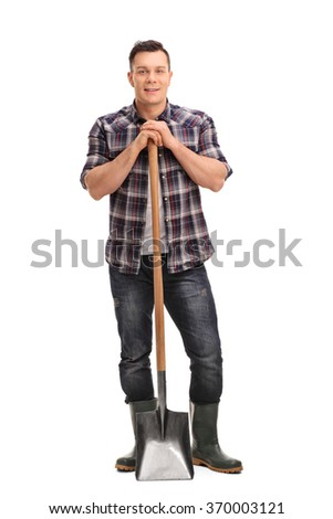 Full length portrait of a young agricultural worker posing with a shovel isolated on white background - stock photo