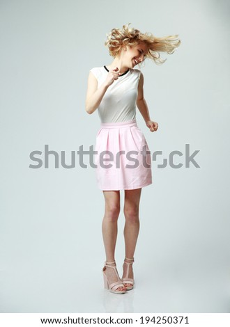 Full length portrait of a young beautiful woman having fun on gray background - stock photo