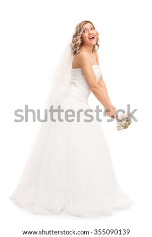 Full length portrait of a young blond bride tossing her wedding bouquet isolated on white background - stock photo