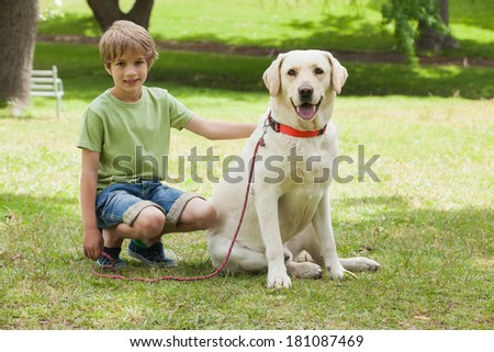 Full length portrait of a young boy with pet dog at the park - stock photo