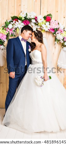 Full length portrait of a young bride and groom posing together.