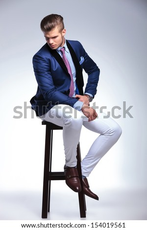 full length portrait of a young business man sitting on a chair and looking down, away from the camera. on a gray background - stock photo