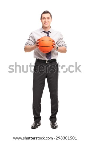 Full length portrait of a young businessman holding a basketball and looking at the camera isolated on white background - stock photo
