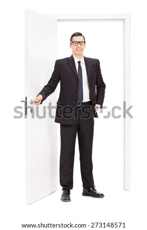 Full length portrait of a young businessman in a black suit posing in front of an opened door isolated on white background - stock photo