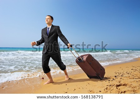 Full length portrait of a young businessman in suit walking on a sandy beach with his luggage