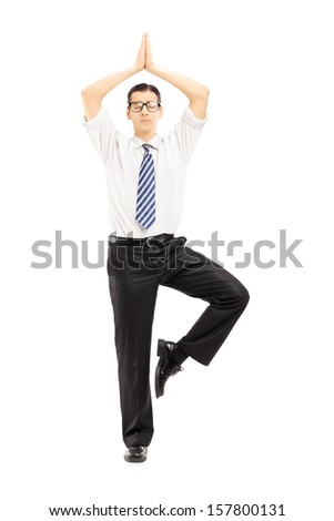 Full length portrait of a young businessman meditating isolated on white background - stock photo