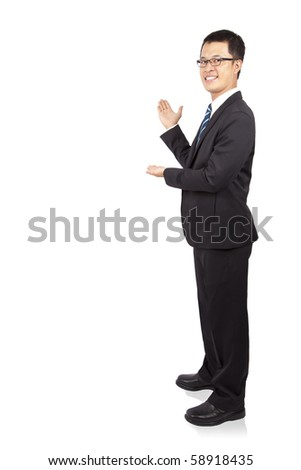 Full length portrait of a young businessman showing copy space and Isolated on white background - stock photo