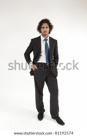 full length portrait of a young businessman wearing a suit and a neck tie. - stock photo