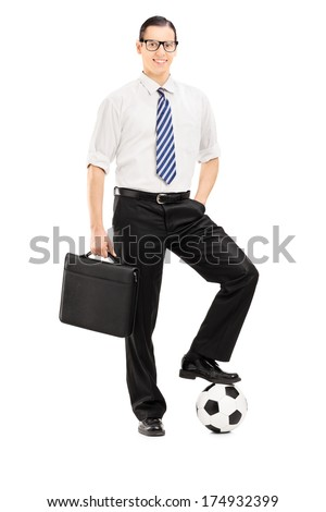 Full length portrait of a young businessman with briefcase and football under his foot isolated on white background
