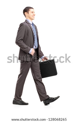 Full length portrait of a young businessman with briefcase walking isolated on white background - stock photo