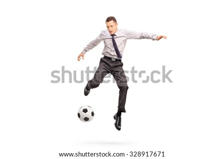 Full length portrait of a young businessperson kicking a football shot in mid-air isolated on white background - stock photo