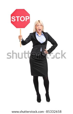 Full length portrait of a young businesswoman holding a traffic sign stop isolated on white background - stock photo
