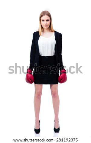 Full length portrait of a young businesswoman standing in suit and boxing gloves over white background. Looking at camera - stock photo