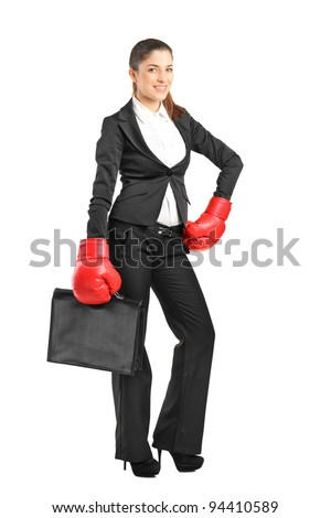 Full length portrait of a young businesswoman with boxing gloves holding a briefcase isolated on white background - stock photo