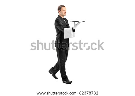 Full length portrait of a young butler with bow tie carrying a tray isolated on white background - stock photo