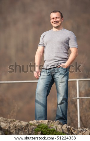 Full length portrait of a young caucasian man outdoors