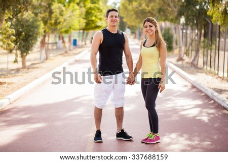 Full length portrait of a young couple in sporty outfit holding hands at a running track outdoors - stock photo