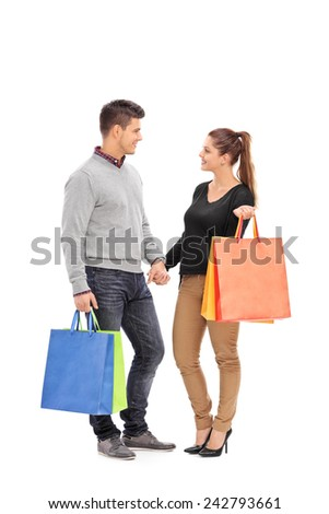 Full length portrait of a young couple with shopping bags having a conversation isolated on white background - stock photo