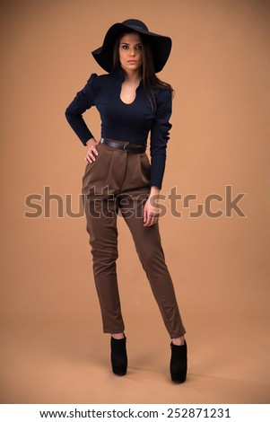 Full length portrait of a young cute woman over brown background - stock photo