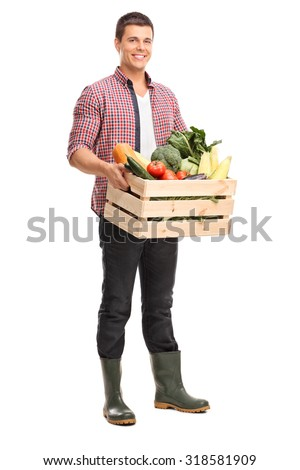 Full length portrait of a young farmer holding a crate full of fresh vegetables isolated on white background - stock photo