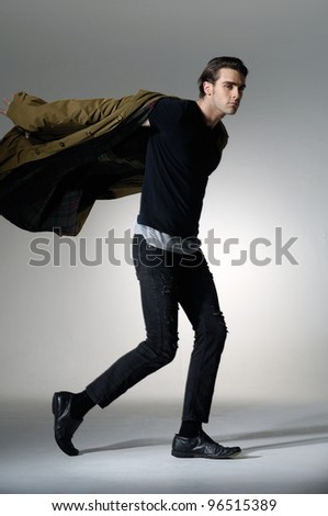 Full length portrait of a young fashion male walking on light background - stock photo