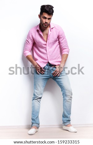full length portrait of a young fashion man with his hands at his crotch, looking at the camera. isolated on a white background