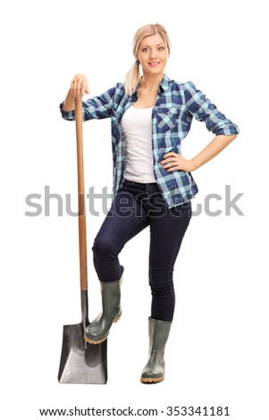 Full length portrait of a young female agricultural worker in a blue checkered shirt posing with a shovel isolated on white background